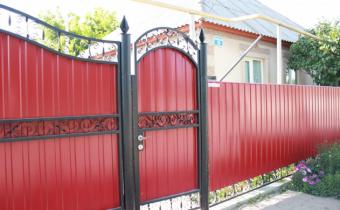 Профнастил на заборе в обрамлении рамы гнутой формы с декоративной ковкой